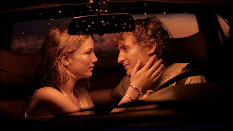 一對戀人戴著卡地亞的 LOVE 手環,相視而笑