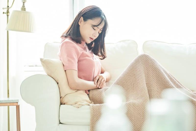 女性因生理痛坐在沙發休息
