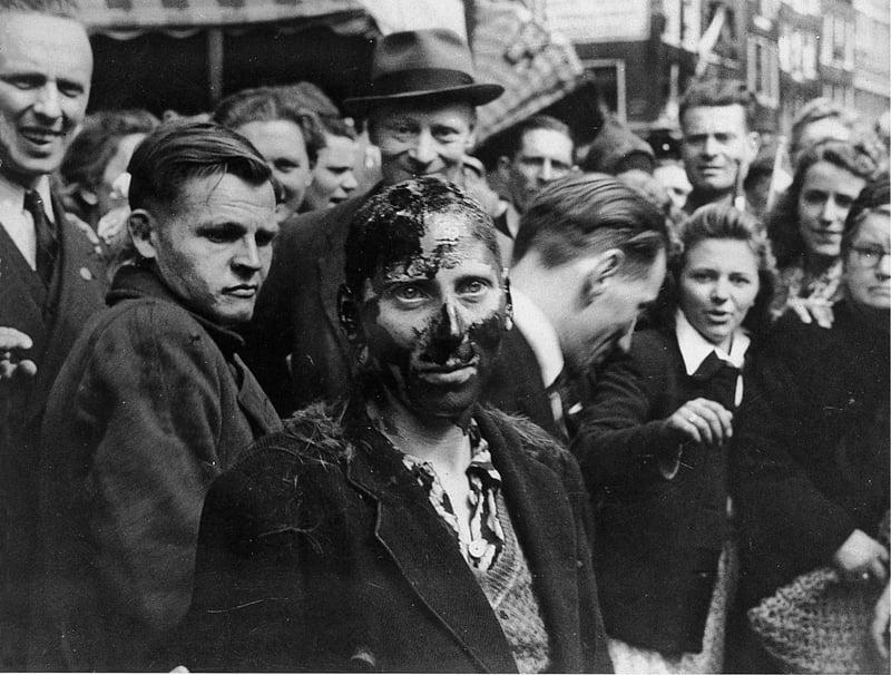 一個戰時通敵的女人在大街上被潑焦油,路人圍觀